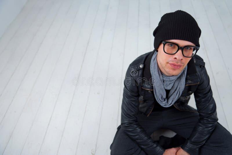 Hombre joven en la ropa casual que se sienta en el piso imágenes de archivo libres de regalías