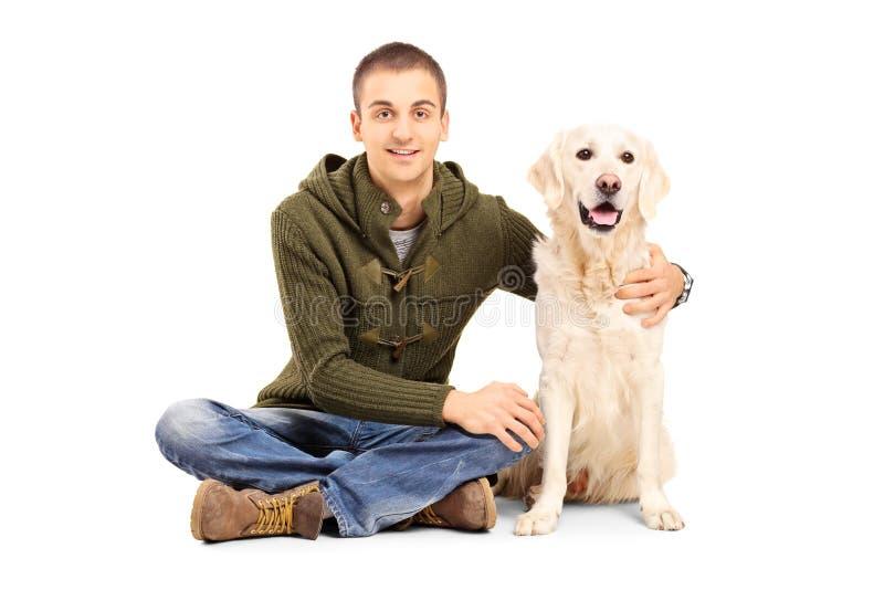 Hombre joven en la ropa casual que se sienta en piso con su Labrador r fotos de archivo
