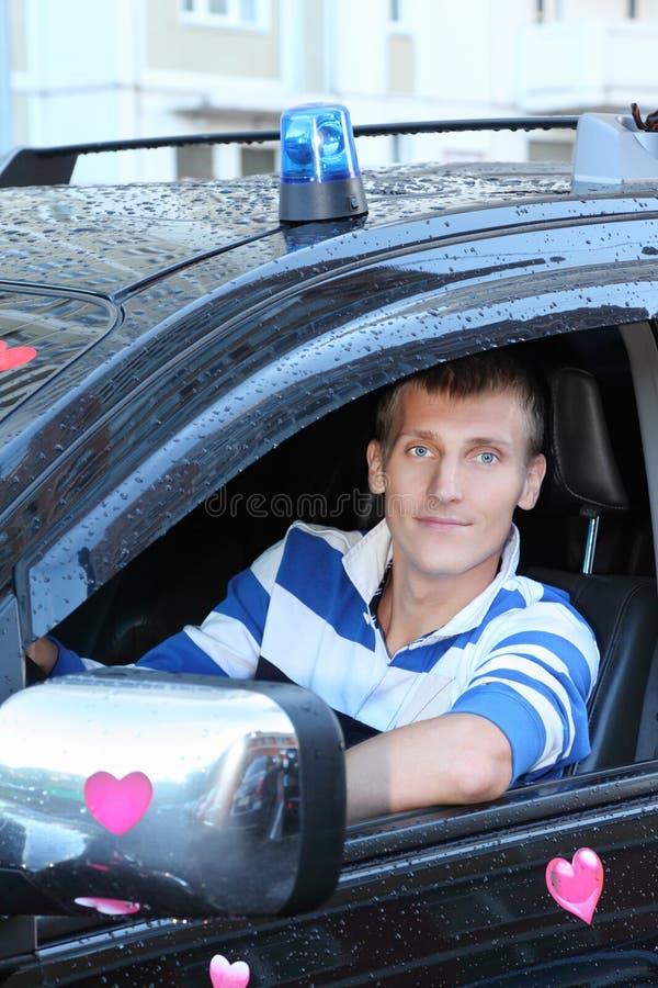 Hombre en la rueda del offroader mojado con los corazones de las etiquetas engomadas foto de archivo libre de regalías