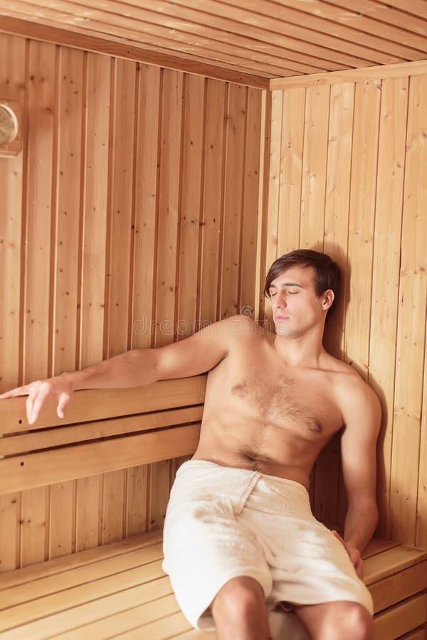 Hombre joven en la sauna fotos de archivo