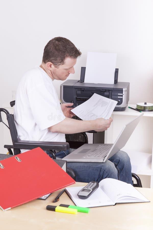 Hombre joven en la silla de ruedas en el trabajo fotografía de archivo libre de regalías