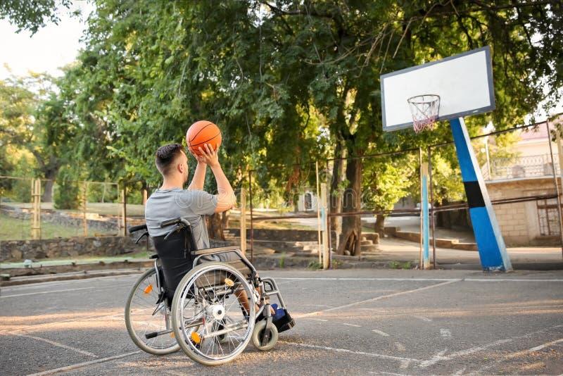 Hombre joven en la silla de ruedas que juega a baloncesto al aire libre fotos de archivo libres de regalías