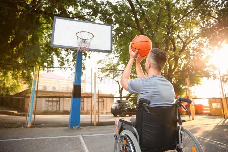 Hombre joven en la silla de ruedas que juega a baloncesto al aire libre imagen de archivo libre de regalías