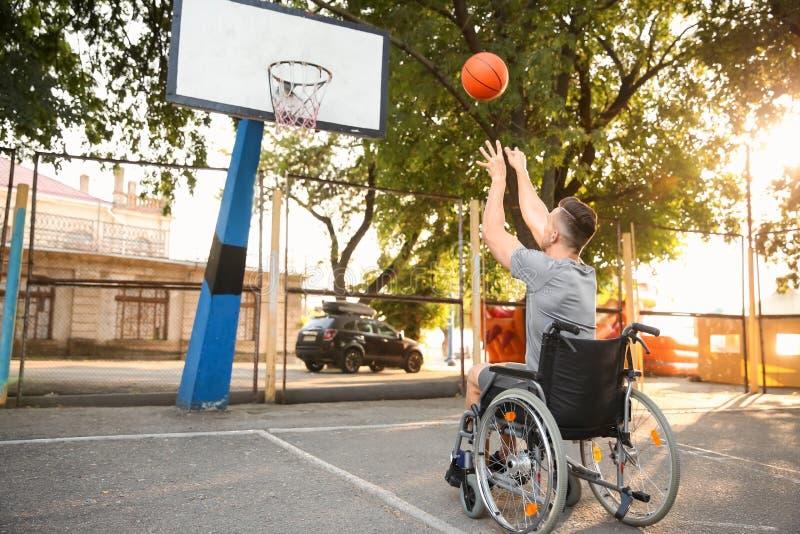 Hombre joven en la silla de ruedas que juega a baloncesto al aire libre imagen de archivo
