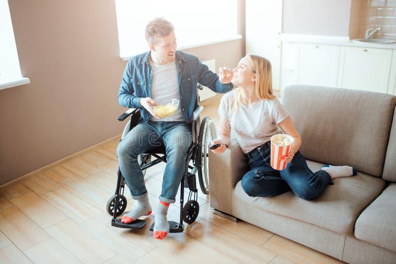 Hombre joven en la silla de ruedas que se sienta al lado de mujer en el sof? Persona con incapacidad y necesidades especiales Pel imagen de archivo libre de regalías