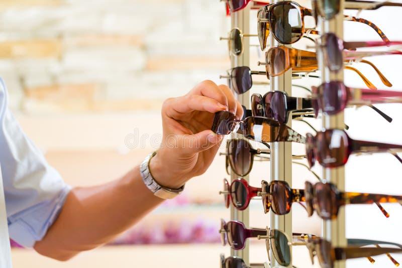 Hombre joven en las gafas de sol de las compras del óptico imagen de archivo libre de regalías