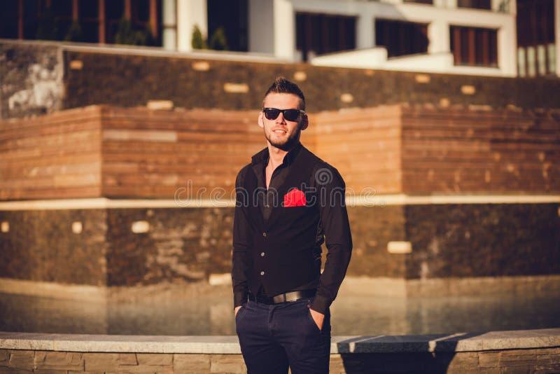 Hombre joven en las gafas de sol que se colocan en ciudad Copyspace foto de archivo libre de regalías