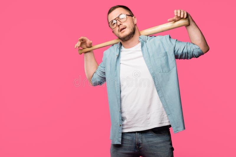 hombre joven en las lentes que sostienen el bate de béisbol en hombros y que miran la cámara aislada fotos de archivo