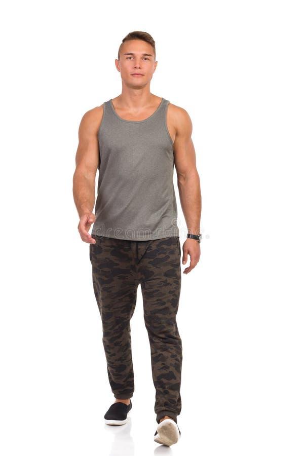 Hombre joven en los pantalones de deporte de Camo que camina hacia cámara fotografía de archivo