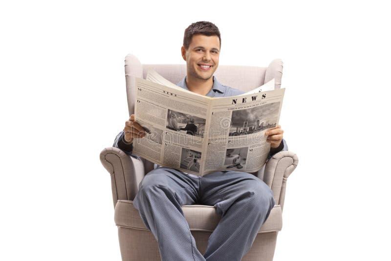 Hombre joven en los pijamas asentados en una butaca con un periódico imagenes de archivo