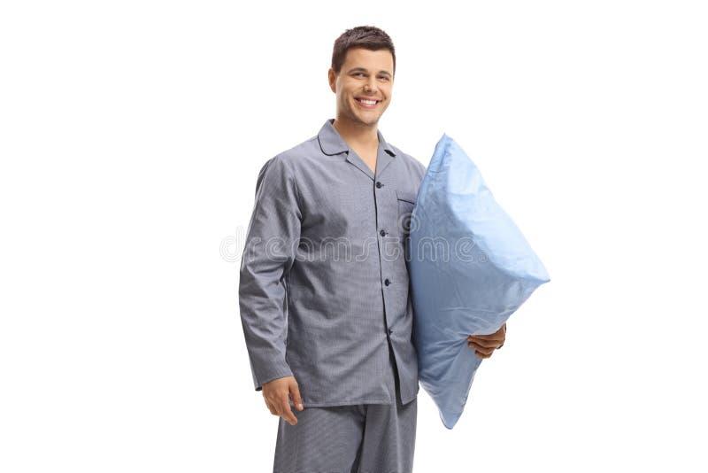 Hombre joven en los pijamas que celebran una almohada y una sonrisa imágenes de archivo libres de regalías