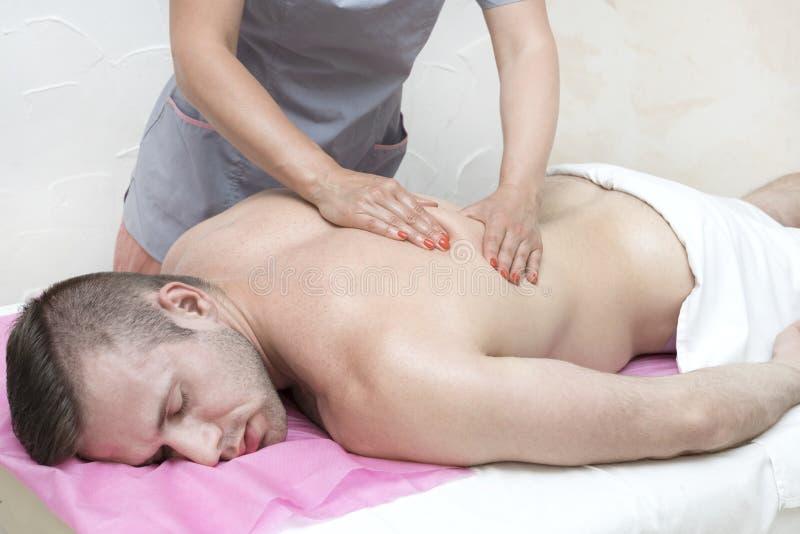 Hombre joven en masaje de los tratamientos de la salud imagenes de archivo