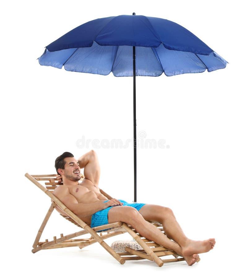 Hombre joven en ocioso del sol debajo del paraguas contra el fondo blanco Playa fotografía de archivo libre de regalías