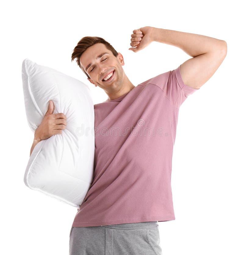 Hombre joven en pijamas con la almohada fotografía de archivo