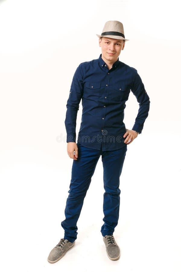 Hombre joven en ropa azul en un fondo blanco fotografía de archivo libre de regalías