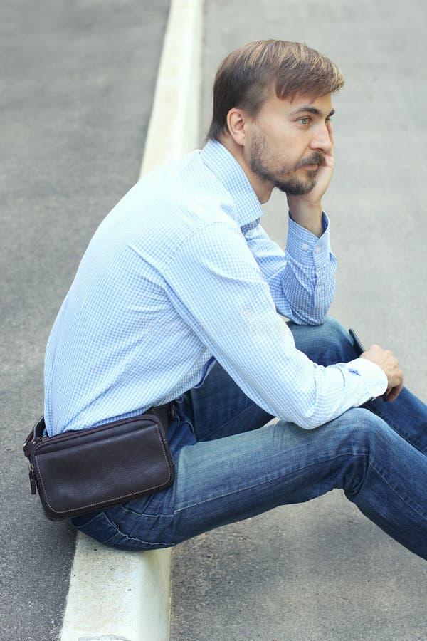Hombre joven en ropa casual con el bolso de cuero moderno del weist y el SM fotografía de archivo libre de regalías