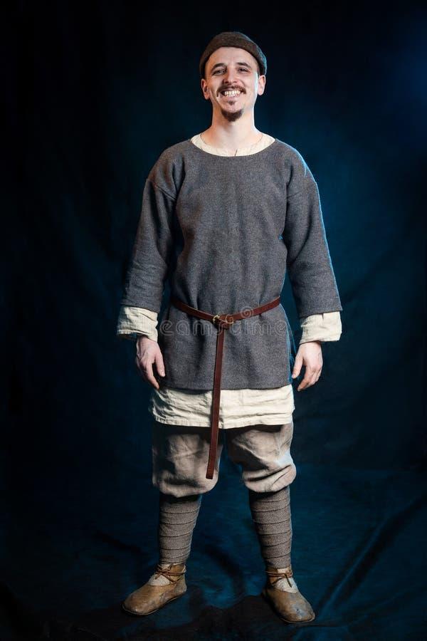 hombre joven en ropa gris casual y un sombrero de la sonrisa medieval temprana foto de archivo libre de regalías