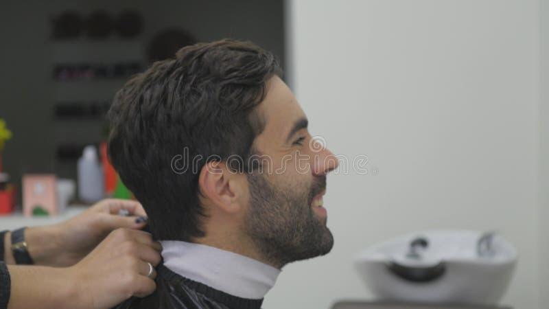 Hombre joven en salón de pelo Mujer del peluquero y su cliente imagenes de archivo