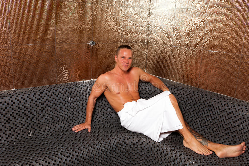 Hombre joven en sauna imagen de archivo