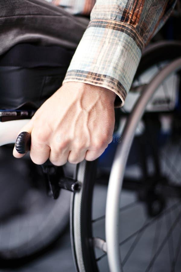Hombre joven en sillón de ruedas imagenes de archivo