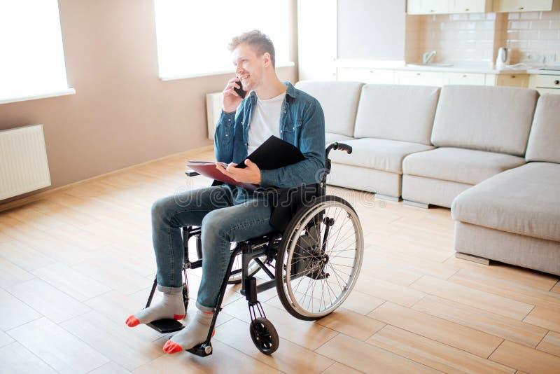 Hombre joven en sill?n de ruedas Persona con necesidades especiales inhabilidad Estudiante que se sienta y que habla en el tel?fo fotos de archivo