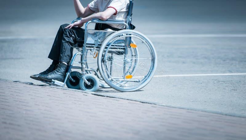 Hombre joven en silla de ruedas en el camino solamente. fotografía de archivo