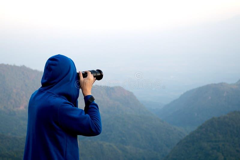 Hombre joven en suéter con la capilla que toma una foto encima de la montaña en Doi Ang Khang Chiang Mai Thailand foto de archivo libre de regalías