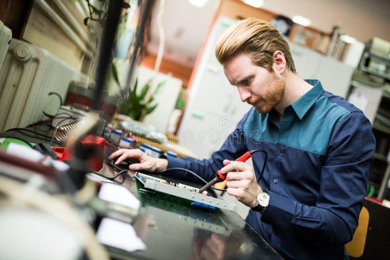 Hombre joven en taller de la electrónica foto de archivo