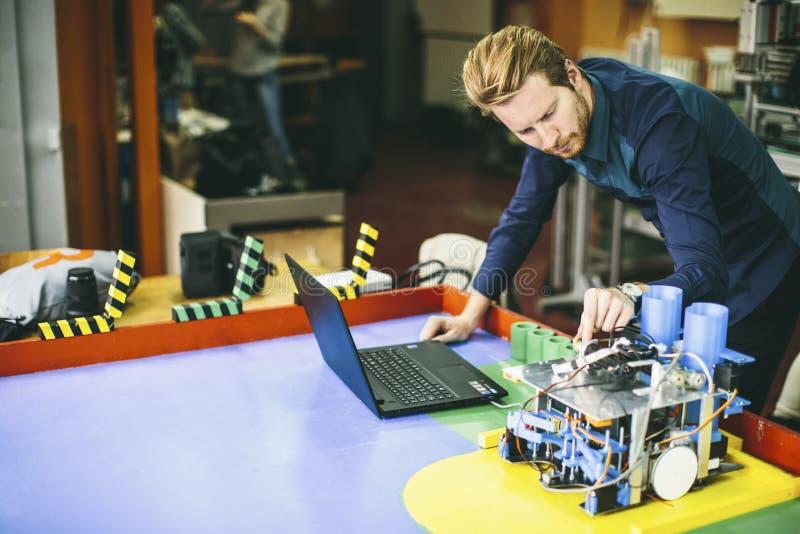 Hombre joven en taller de la electrónica imagen de archivo