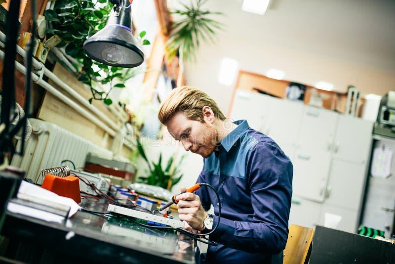 Hombre joven en taller de la electrónica foto de archivo libre de regalías