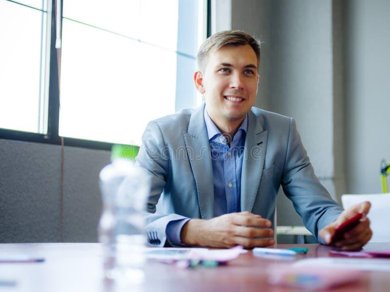 Hombre joven en traje, en el escritorio en oficina Primer de una botella de agua fotos de archivo libres de regalías