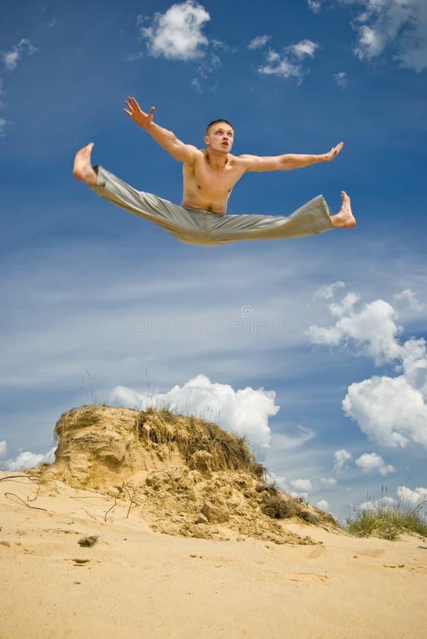 Hombre joven en un alto salto del karate foto de archivo libre de regalías