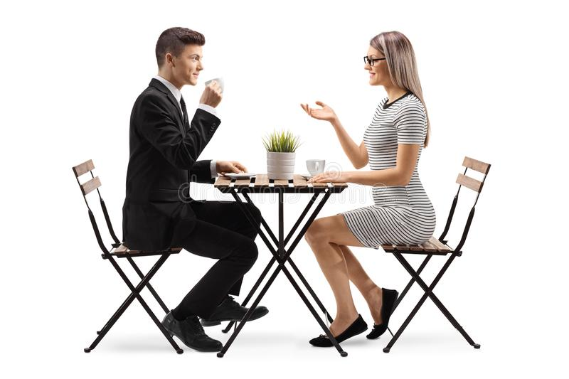 Hombre joven en un cofee de consumición y sentarse del traje en una tabla con una mujer joven foto de archivo
