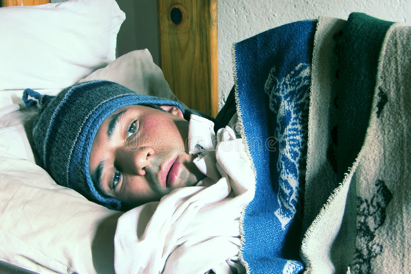 Hombre joven en un frío de la sensación de la cama imagenes de archivo