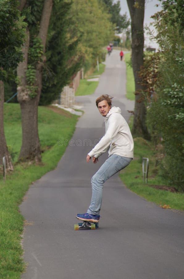 Hombre joven en un longboard que conduce abajo de un camino vacío imagen de archivo