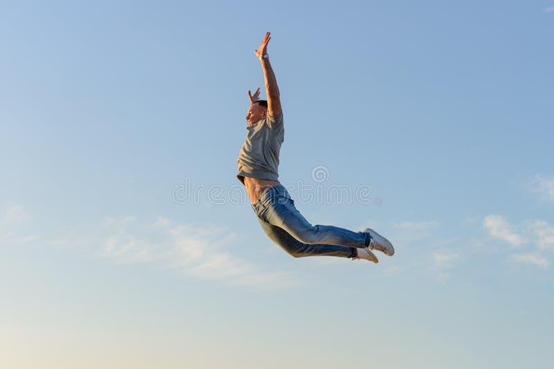 Hombre joven en un salto contra un cielo azul imagen de archivo