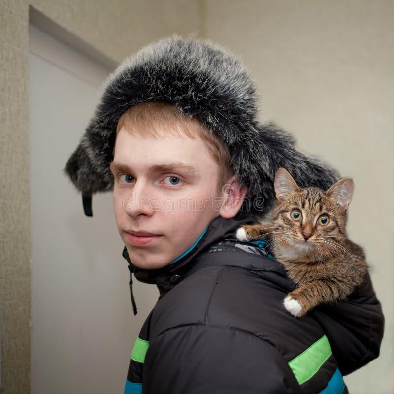 Hombre joven en un sombrero de piel con un gatito del color del gato atigrado en la capilla de su chaqueta foto de archivo libre de regalías