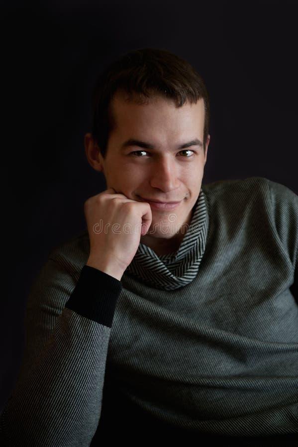 Hombre joven en un suéter oscuro en un fondo negro apoyó su cabeza con su puño imagen de archivo