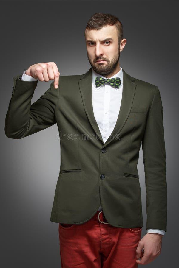 Hombre joven en un traje verde, señalando abajo fotos de archivo