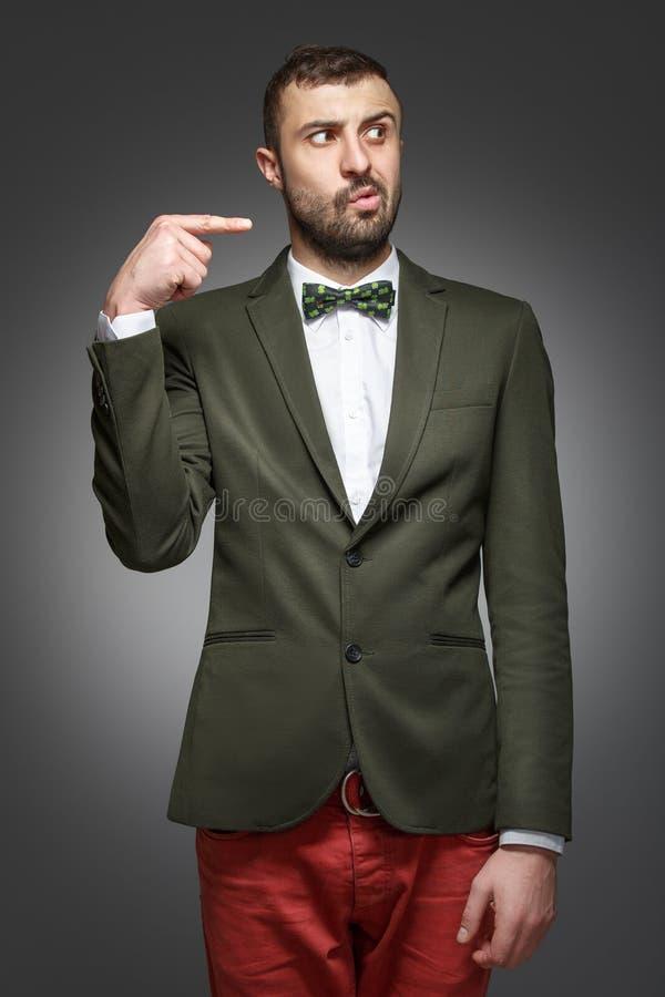 Hombre joven en un traje verde, señalando en la derecha imagen de archivo