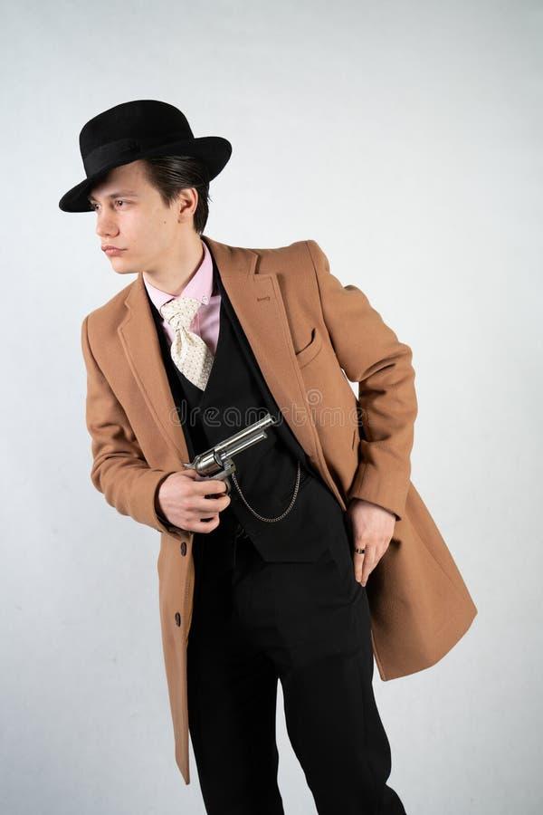 Hombre joven en un traje y un sombrero formales con un arma en sus manos en un fondo blanco en el estudio solamente imagen de archivo libre de regalías