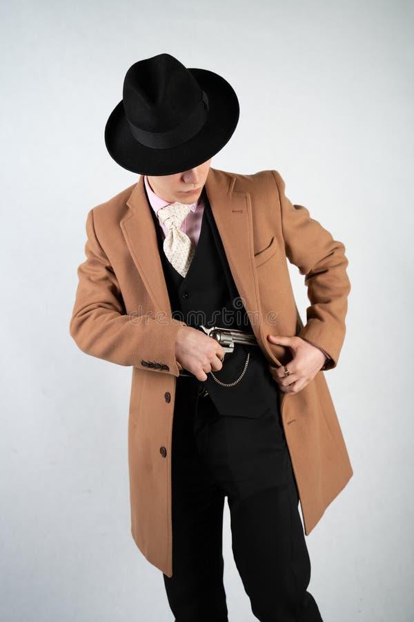 Hombre joven en un traje y un sombrero formales con un arma en sus manos en un fondo blanco en el estudio solamente foto de archivo libre de regalías