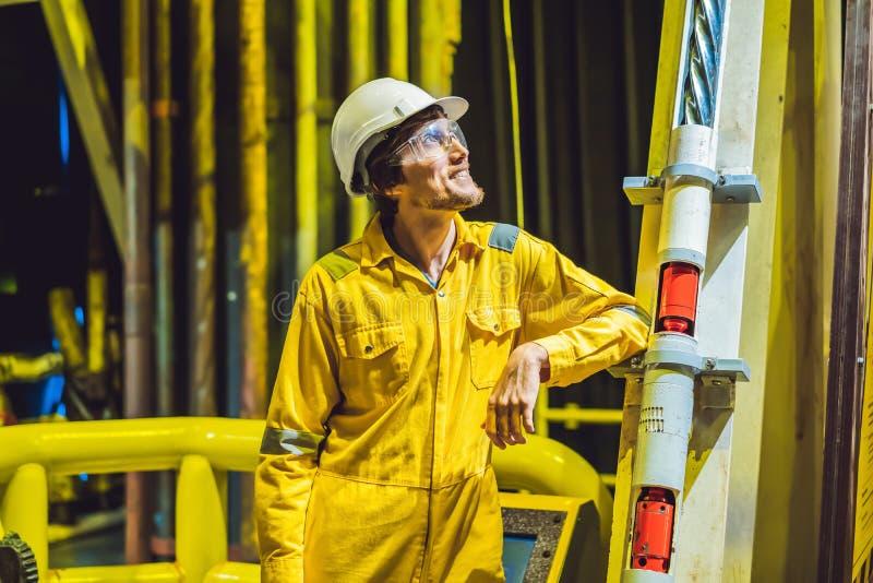 Hombre joven en un uniforme amarillo, vidrios y casco del trabajo en planta del ambiente industrial, de la plataforma petrolera o fotografía de archivo