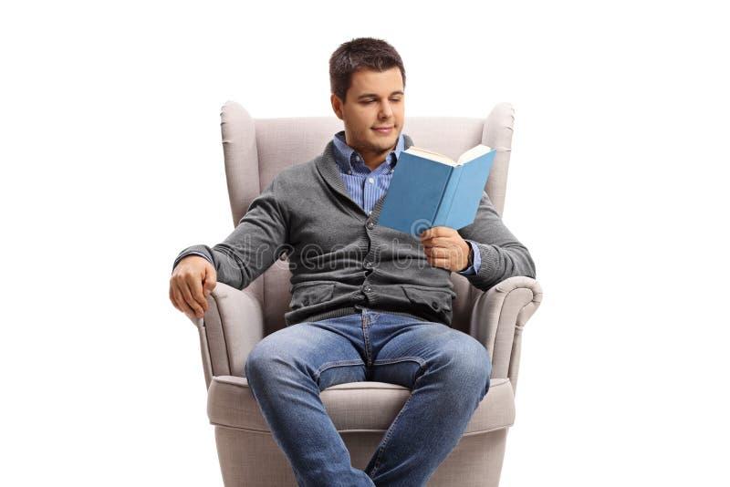 Hombre joven en una butaca que lee un libro imagen de archivo