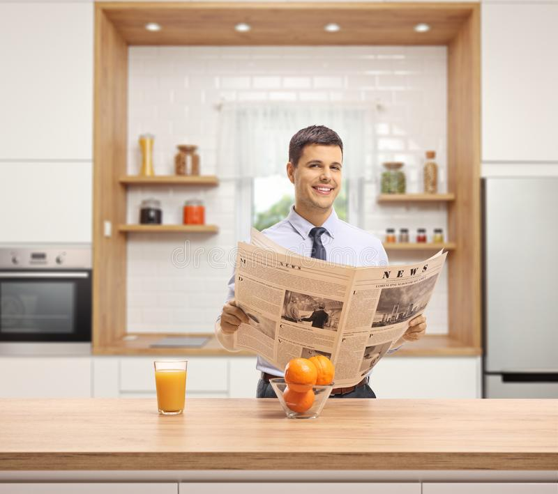 Hombre joven en una cocina que lee un periódico, sosteniendo un vidrio de zumo de naranja y sonriendo en la cámara foto de archivo