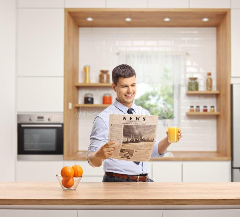 Hombre joven en una cocina que lee un periódico y que sostiene un vidrio de zumo de naranja fotos de archivo