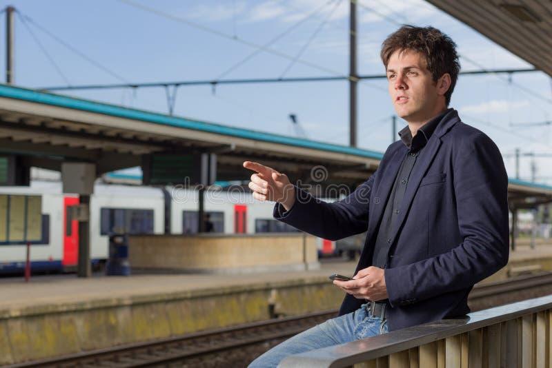 Hombre joven en una estación de tren que señala lejos fotos de archivo libres de regalías