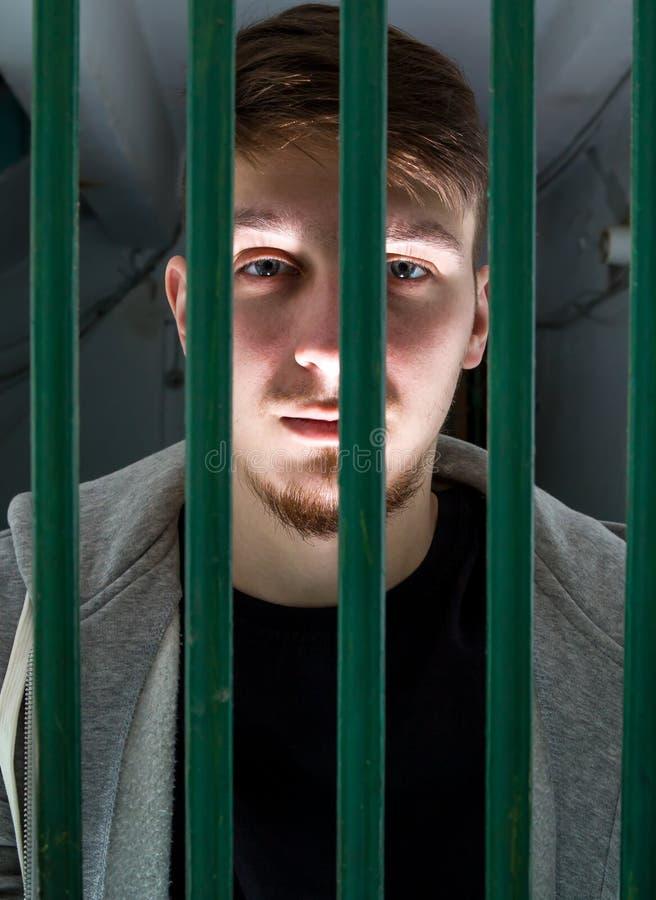 Hombre joven en una jaula fotografía de archivo