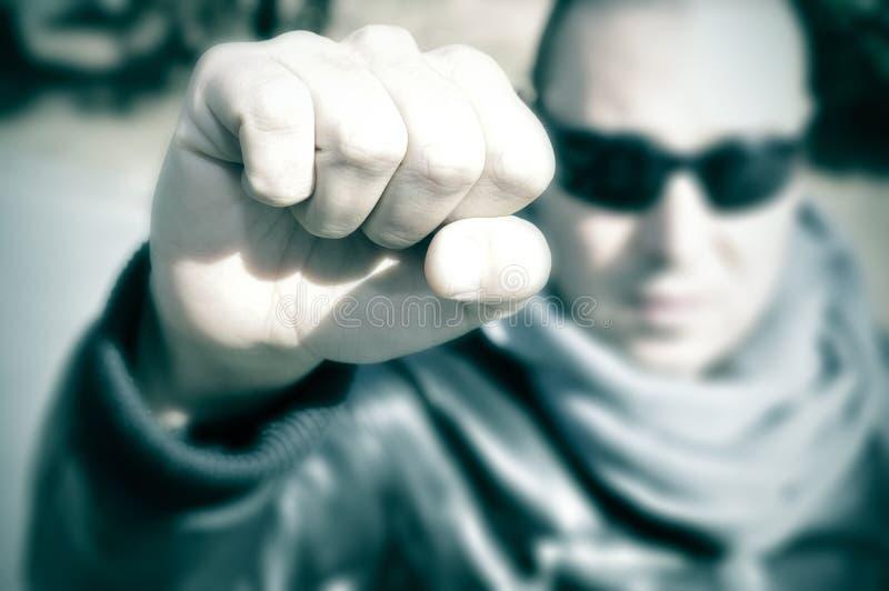 Hombre joven en una protesta que aumenta su puño, con un efecto del filtro foto de archivo libre de regalías