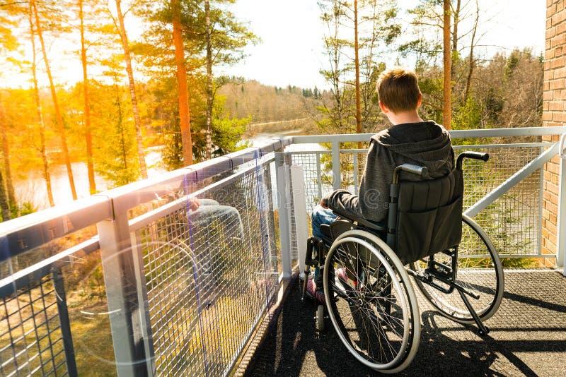 Hombre joven en una silla de ruedas en un balcón que mira la naturaleza adentro foto de archivo